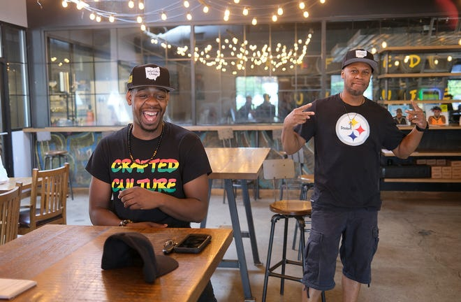 """Anthony """"Sizzle"""" Perry Jr. smiles after selling his first hat to Shawn Hill moments after their delivery to Crafted Culture. The hats are part of a fund-raiser to put money back into the Gahanna community."""