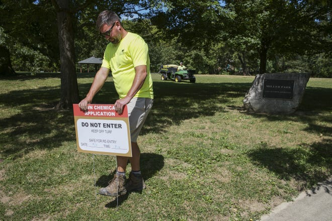 Ryan Kopke, a turf specialist with Upper Arlington Parks and Recreation, sticks a sign in the ground as a chemical is applied to treat the grass for Armyworms on Friday, Sept. 3, 2021 at Miller Park in Upper Arlington, Ohio. Upper Arlington parks have had significant turf damage from the worms, which feed on the grasses.