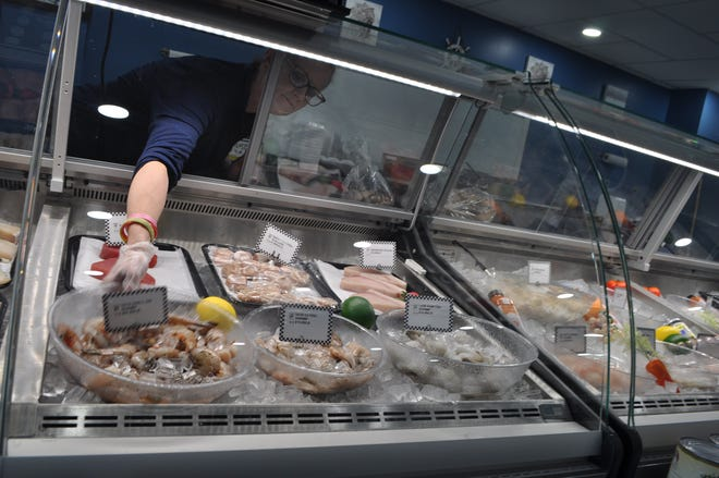 Market manager Kelly Miller reaches for a bowl of shrimp to fill an order Sept. 3 for a customer at the new Frank's Fish & Seafood Market II, 2410 Hilliard-Rome Road in Columbus.