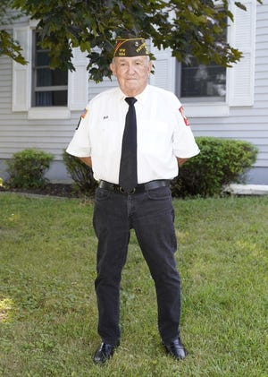 Veteran Bill Butchart stands in front of his home last week. At age 85, the veteran of foreign wars is still at iton the funeral detail in the city of Adrianas well as working as a groundskeeper for a local church.