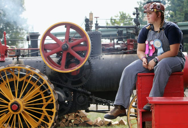 Everlee Harvey, 16, of Argyle, who has been helping fellow engineer Jeff Ruth of Rogersville, Missouri, since she was 8, takes a break from tending to a 1913 20 hp Avery Co. steam engine Thursday during the 2021 Midwest Old Threshers Reunion in Mount Pleasant. In addition to being an engineer on the grounds, Harvey also is one of this year's Sweet 16 candidates.