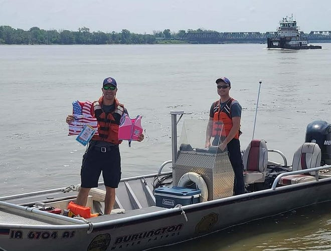 Burlington firefighters and paramedics Nick Gurdian, left, and Andy Crooks get ready to head out on the Mississippi River July 17 in Burlington.