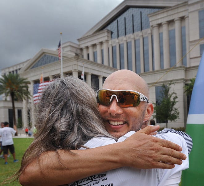Attorney Mike Freed, being hugged in this 2017 photo after finishing a six-day series of marathons between Tallahassee and Jacksonville to raise money for Jacksonville Area Legal Aid, is using his role with a national legal organization to urge attorneys to donate time working with renters and landlords to try to resolve a backlog of pandemic-driven rent disputes without mass evictions.