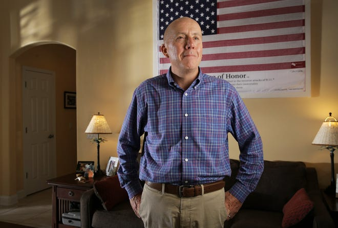 Patrick McGarry stands in front of a flag in his Ponte Vedra Beach home with the names of the victims of the 9/11 attacks on the World Trade Center, including his sister's, Katherine McGarry Noack.