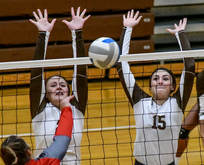 Garden City High School's MiKayla Martinez, left, and Mackenzie Lucas combine to block a Liberal shot Thursday during a match in a Western Athletic Conference volleyball triangular at GCHS.