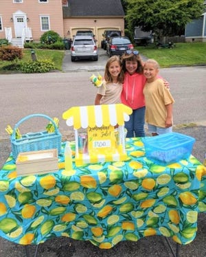 Ava, left, and Lily Dubrule with their former principal, Colleen Gilhooly, who stopped by the lemonade stand and donated her birthday money.