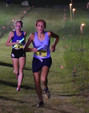 Frankfort's Addison Lease is shown running by the light of tiki torches at the Knights' Night Relay even last Saturday.