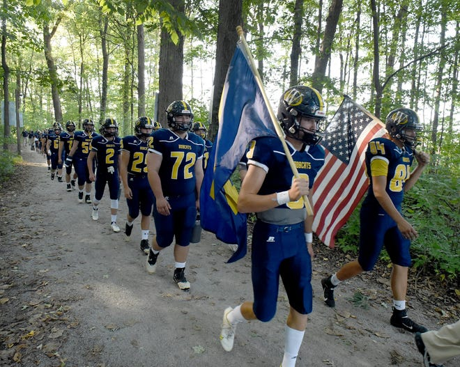 A old tradition as Ryin Ruddy and Jack Andrews carry the Whiteford flag and the American flag flags with teammates and coaches following through the tunnel of trees to the field to play Ida Thursday, September 2, 2021.