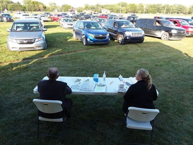 Anna Sahloff (right), administrative manager for Monroe County Farm Bureau, and Mike Fusilier, District 3 director on the state board, glance at the vehicles lined up for the 2020 annual meeting held during a drive-in format at the Monroe County Fairgrounds in September, 2020. The bureau will hold its 2021 meeting at the fairgrounds again Sept. 23.