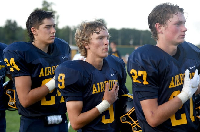 Airport football players Nolan Zajac, Adam Goins (center) and Kyle Harvell stand for the National Anthem. Goins returned to the Jets for his senior year after not playing football the past two seasons.