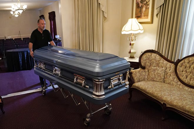 Callahan Funeral Home director Ellis McAninich moves a casket for display to a room in the home Aug. 21 in Nassau County, Florida.