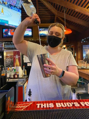 Waitress/Bartender Shelly Herd mixes a drink for a waiting customer on the bar side of Club D'Est Restaurant in Pratt.