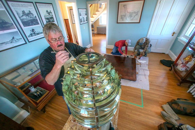 Noted Lampist Kurt Fosburg works on the Fresnel lens as Pomham Rocks members Gary Point, background left, and Dennis Tardiff work on the platform that will hold the exhibited historic glass.