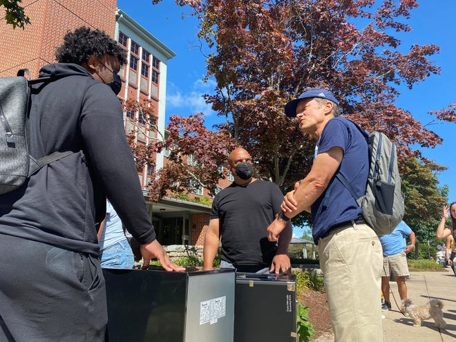 University of Rhode Island President Marc Parlange, right, talks with freshman Dylan Mercado, left, of Rockland County, New York, and Mercado's father, David Mercado, as Dylan moves into Browning Hall on the South Kingstown campus Friday for the start of the school year.