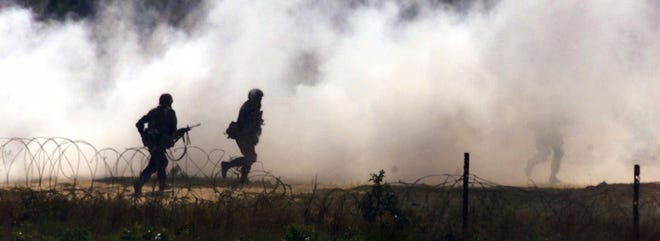 Members of the 82nd Airborne Division run through a cloud of smoke during a training exercise at Fort Bragg Sept. 19, 2001, as the 82nd continues normal training while they wait for word on a possible deployment.