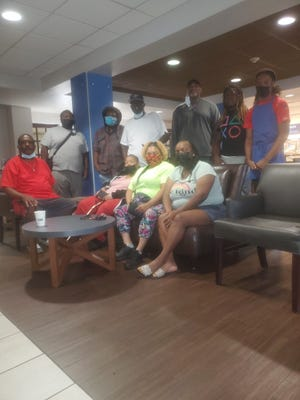 Members of the Johnson family alongside those in the community that have helped them during their time being evacuated from Baton Rouge, Louisiana because of Hurricane Ida