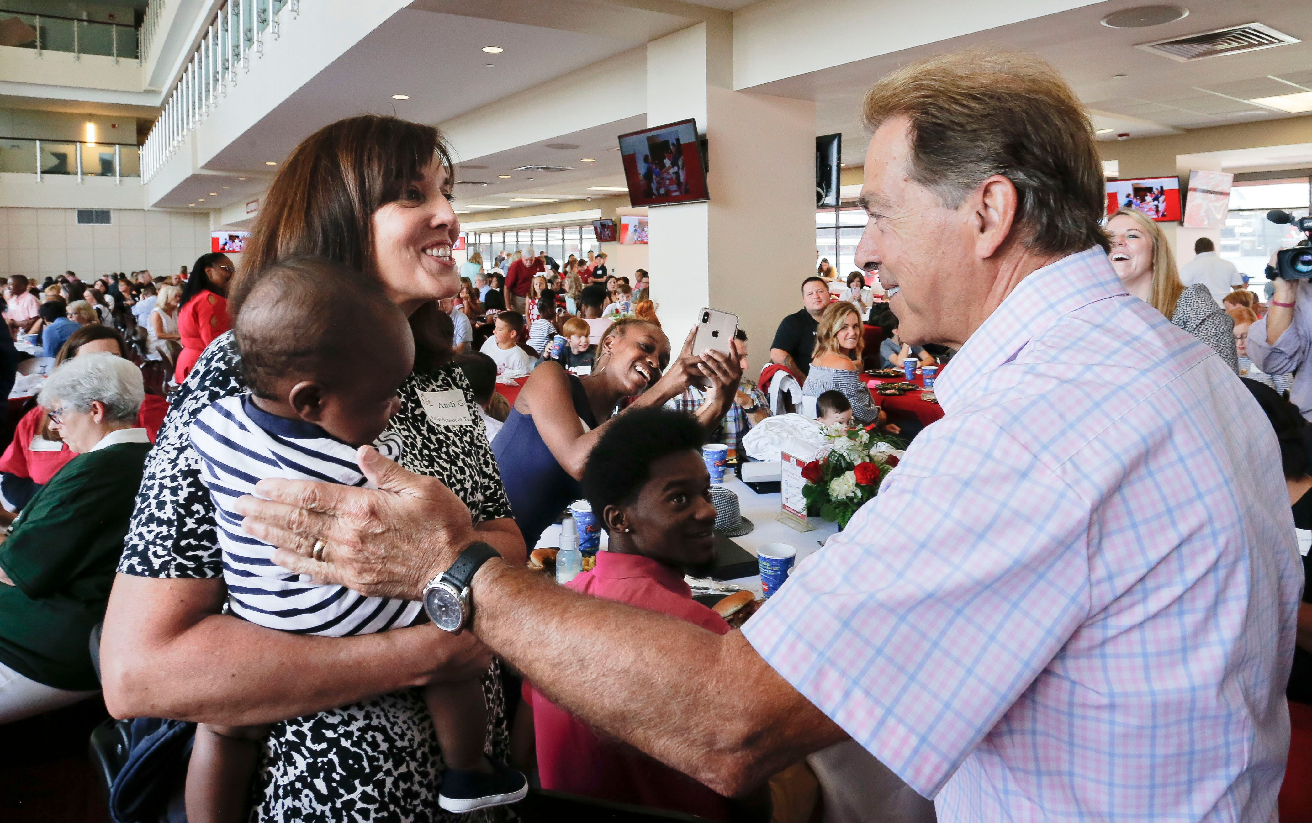 Andi Gillen, director of the Rise Center, presents one of her incoming preschool students, Royal Williams, to Coach Nick Saban during the annual Nick's Kids Foundation luncheon in Bryant-Denny Stadium Thursday August 1, 2019. [Staff Photo/Gary Cosby Jr.]