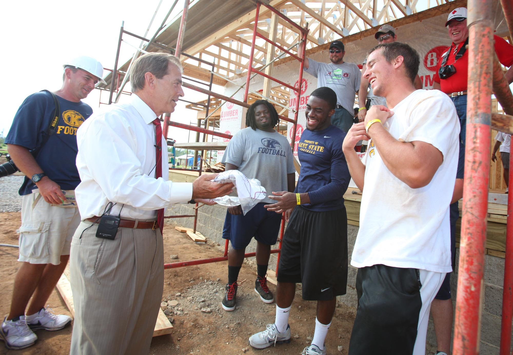 University of Alabama head football coach Nick Saban offers a shirt to Kent State player Terry Jacques, fourth from left, at a Habitat for Humanity house in the Holt community of Tuscaloosa, Ala. Friday, July 22, 2011. Kent State players, Alabama players and Alabama and Auburn students volunteered to rebuild a home that was devastated by the April 27th tornado.  [Staff file photo]
