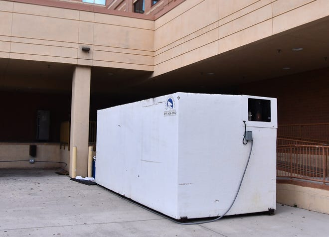 Parked inconspicuously behind the hospital near the loading dock is a refrigerated trailer, a temporary morgue for the overflow of dead patients.