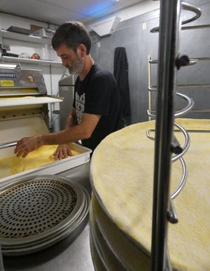Michael Miller prepares pizza crusts at Baker's Pizza Sports Shack on Wednesday.