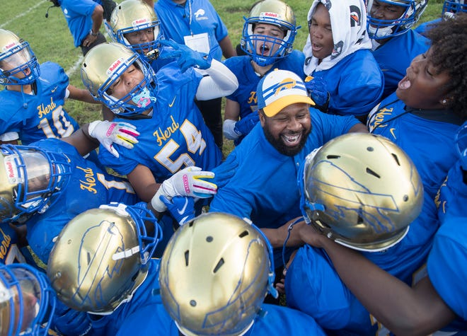 Woodbury High School's football coach Anthony Reagan celebrates with his players after Woodbury defeated Paulsboro, 6-0, at Woodbury High School on Friday, September 3, 2021.
