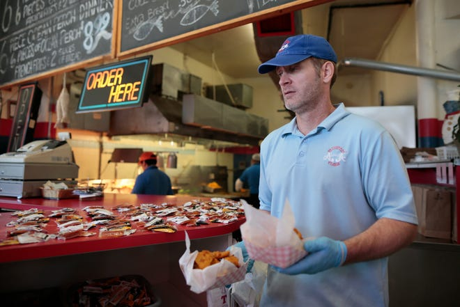 Manager Matthew Trent carries a customer's order out to her during the lunch rush at Alabama Fish Bar in the Over-the-Rhine neighborhood of Cincinnati on Friday, Sept. 3, 2021. The neighborhood fish spot has been in continuous service for 29 years but will be shutting down temporarily this fall for renovations as part of the Willkommen mixed-use development on the block.