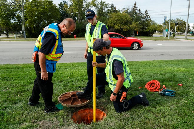 Michael Magda, Western Wayne County hazmat team leader, left, and hazmat technicians Michael Obermiller, Jason Jankowski check out a sanitary sewer across from the Ford Assembly Plant on Gibraltar Road in Flat Rock to isolate the source of the leak on Sept. 3, 2021.