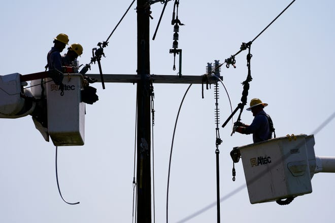 Crews work on power lines that were damaged in the aftermath of Hurricane Ida in LaPlace, La.