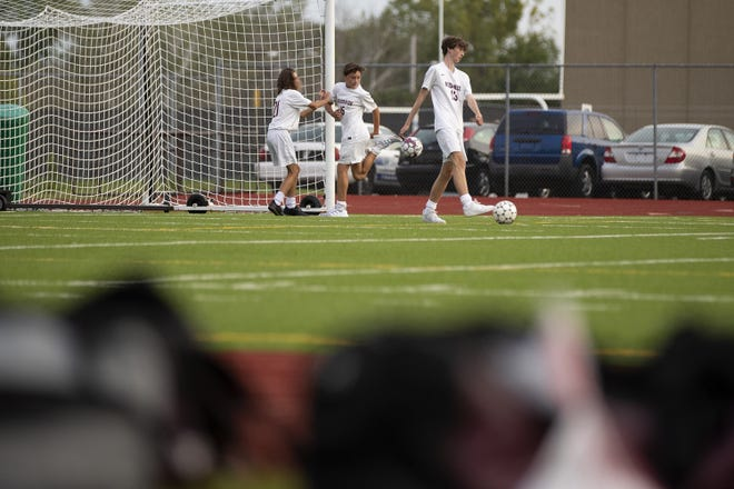 De Pere junior varsity players John Lowery (21), Charlie Tollefson (15) and Colin Elliott (13) play with soccer balls in their street shoes as they wait for a bus to pick them up after their game against Green Bay East on Thursday at Green Bay East High School.