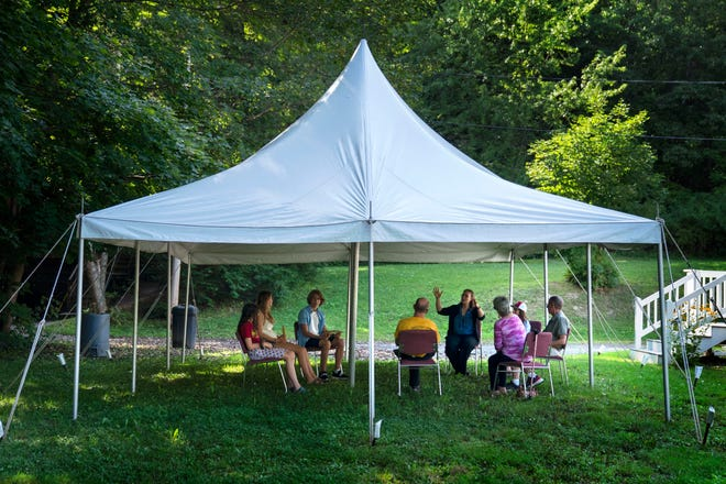"""A class in Judaism is held under a tent set upon outside Temple Beth El, Monday, Aug. 30, 2021, in Augusta, Maine. The recent COVID-19 upsurge is disrupting plans for full-fledged in-person services. """"The ability to see people face to face is wonderful, whatever way they choose to come,"""" Rabbi Erica Asch says. """"But there's a little bit of sadness that we can't all be together the way we'd like."""" (AP Photo/Robert F. Bukaty)"""