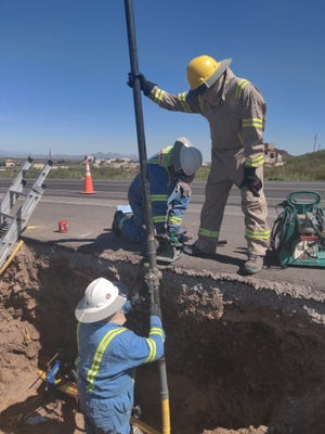 A Las Cruces Utilities gas crew expels trapped air out of the newly installed natural gas line.