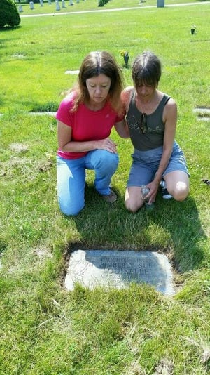 Kimberly Louiselle's sisters visit her grave. Cindy Arthurs, a younger sister, is on the right.