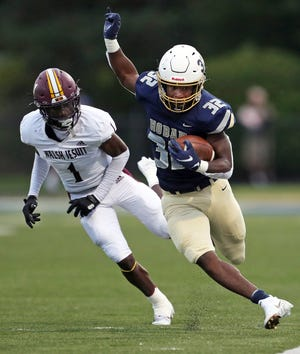 Hoban running back Lamar Sperling sprints down the sideline past Walsh Jesuit defensive back Bryan Blackwell during the first half of a high school football game, Friday, Sept. 3, 2021, in Akron, Ohio. [Jeff Lange/Beacon Journal]