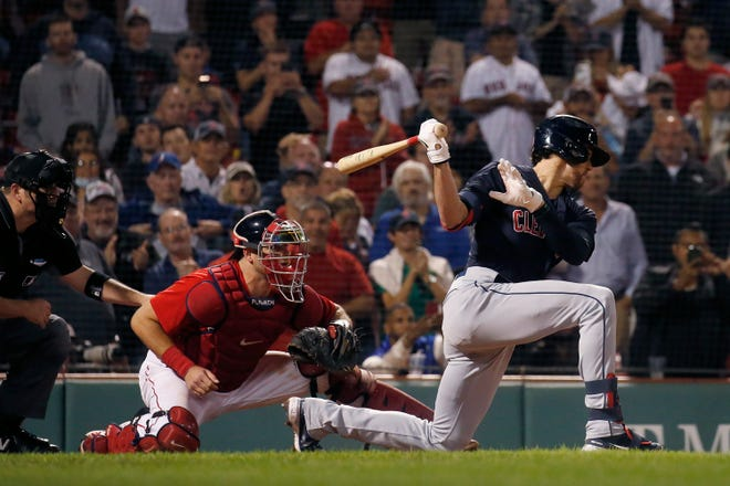 Cleveland's Bradley Zimmer (4) swings from his knees ahead of Boston Red Sox catcher Kevin Plawecki (25) for the the final strike and out in the ninth inning of a baseball game at Fenway Park, Friday, Sept. 3, 2021, in Boston. (AP Photo/Mary Schwalm)