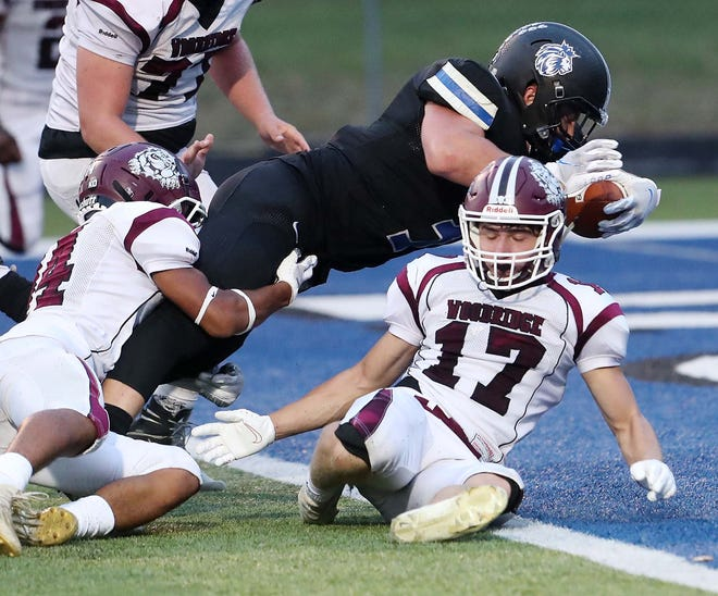CVCA running back Kyle Snider goes in for two points over  Woodridge's Taysear Williams, left, and Jack Novak during the second quarter of their game at CVCA Friday, Sept. 3, 2021 in Cuyahoga Falls, Ohio.