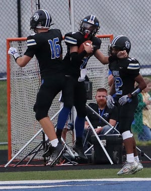 CVCA quarterback Joey Lehner, center, celebrates his 78 yard run for a touchdown with teammates Brennan Darr, left, and Dillon Webb during the first quarter of their game against Woodridge at CVCA Friday, Sept. 3, 2021 in Cuyahoga Falls, Ohio.  [Karen Schiely/Beacon Journal]