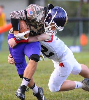 Sebring's Carter Holodnak breaks a tackle by Mathews' Logan Corson during last week's game.