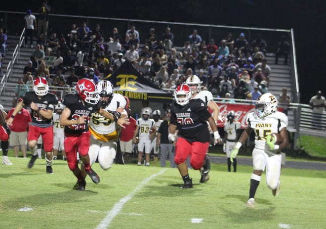 Evans junior Malachi Hardin (15) carries the football in the Knights' 22-20 win over Harlem on Friday night. The Knights improved to 3-0 with the win.