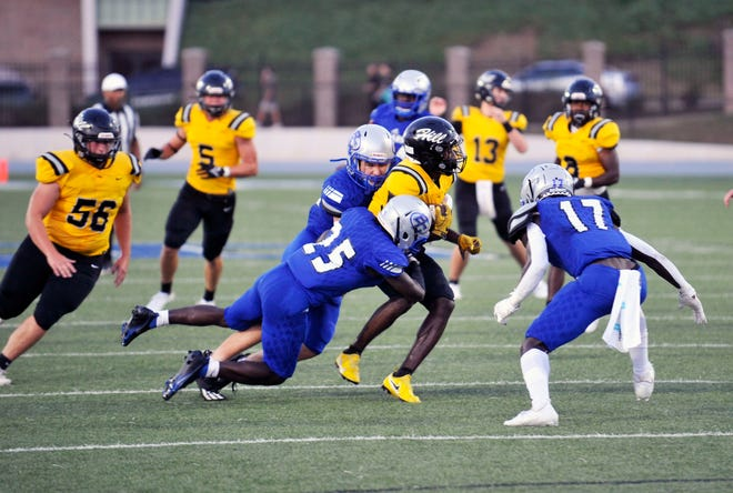 Burke County players attempt to tackle a Richmond Hill player on Friday night at Burke County High School in Waynesboro, Ga. [WYNSTON WILCOX/THE AUGUSTA CHRONICLE]