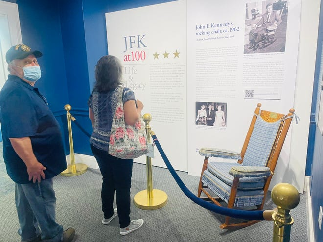 Museum visitors read about JFK's rocking chair in the new installation designed by retired curator and director Rebecca Pierce-Merrick.