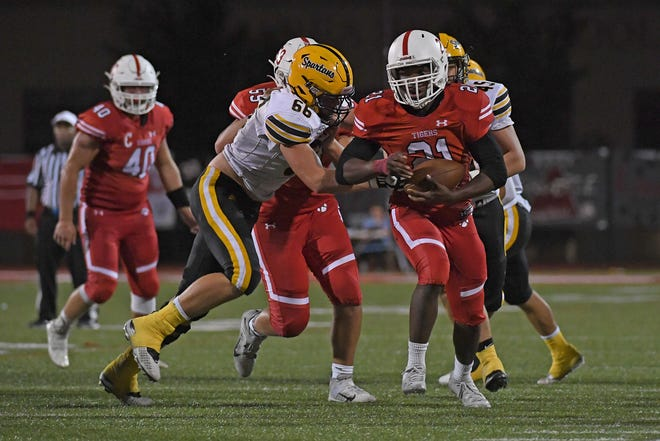 Joe Cotton #21 of the Moon Tigers carries the ball against Jonas Halaja #66 of the Montour Spartans in the second half during the game at Tiger Stadium on September 3 in Moon Township, Pennsylvania.