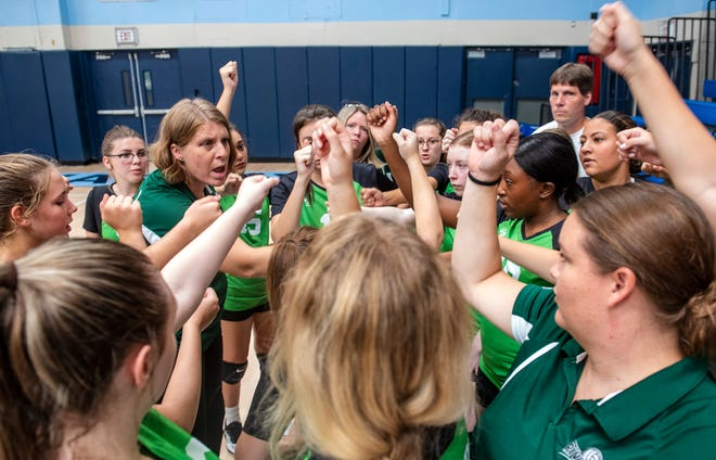 Riverside volleyball players gather with their coach, Marcie Young, left, after their exhibition match Saturday at Central Valley High School.  This was Riverside's first ever match.  They are a club team this year.