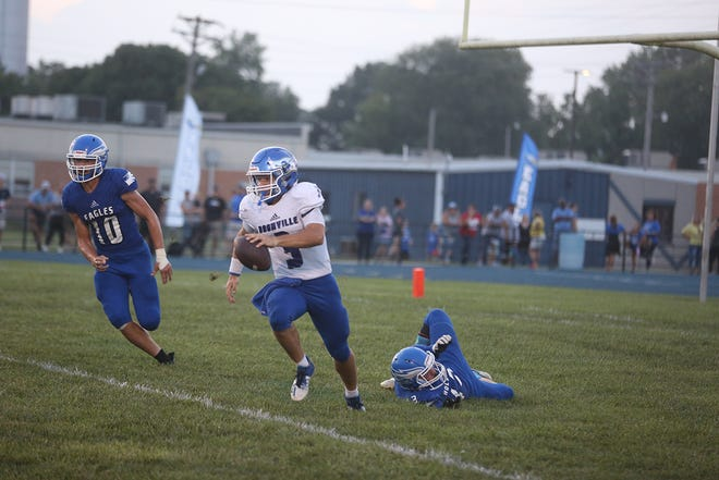Boonville junior quarterback Colby Caton eludes two Holden defenders in the first half Friday night in Holden. The Pirates evened their record to 1-1 on the season by beating Holden 13-6.