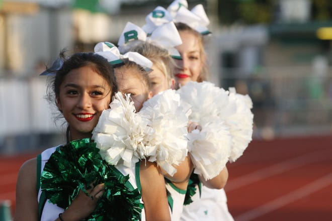 Bangs Dragons cheerleaders face the American flag with their hands over their hearts as the Dragons band plays the National Anthem at Dragon Memorial Stadium Friday night. Florence defeated Bangs 45-14.