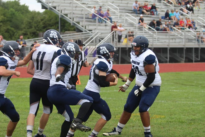 Sterling Lies (ball carrier) celebrates with his team after scoring the game-winning conversion in overtime on Saturday, Sept. 4 at Douglass High School.