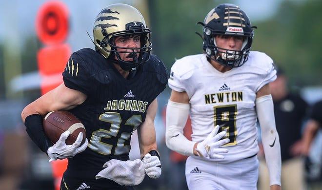 Andover Central's Ashton Barkdull runs as Newton's Keon Edwards gives chanse on Friday, Sept. 3 at Jaguar Field in Andover, Kansas.