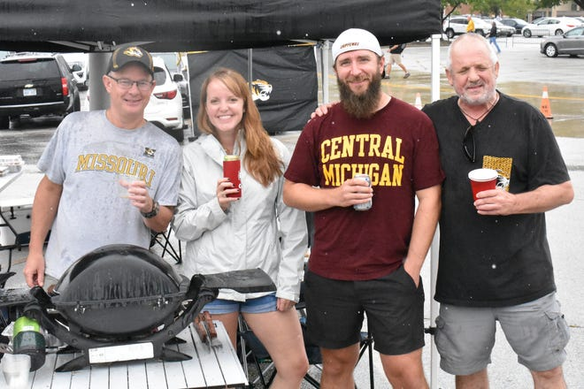 Tayes Taylor (far right), 62, originally from New Zealand, returns to tailgating with Missouri and Central Michigan fans.