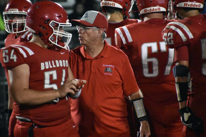 """Harrisburg head football coach Steve Hopkins, talking with his Bulldog players, said he is looking forward to a """"slobberknocker"""" of a game Friday against Westran."""