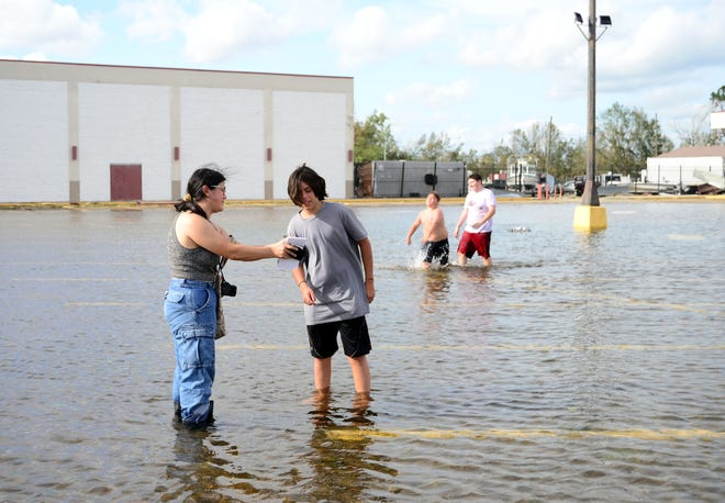 Kezia Setyawan, a reporter for The Courier and the Daily Comet, takes names of children playing in a flooded parking lot for photo captions in Houma, La., on Monday, Aug. 30, 2021, during her reporting work following Hurricane Ida.