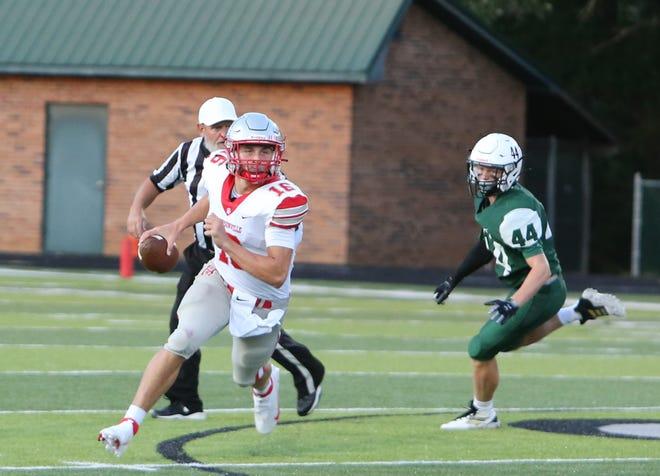 Hendersonville quarterback Gavin Gosnell gets past East Henderson's Stephen Capps during Friday's game.